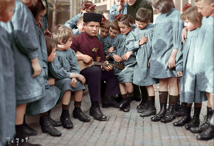 Мальчик-подросток играет на балалайке для детей, 1940 год