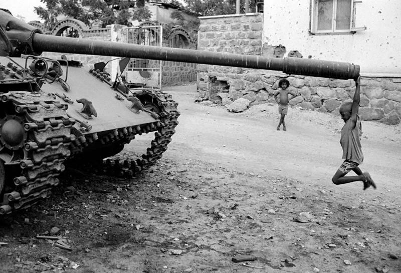 Африканский мальчик играет с заброшенным танком, 1991.
