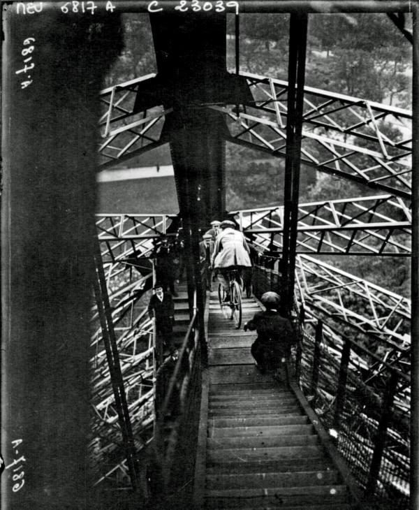 Человек едет на велосипеде в тур Эйфель, 1923.