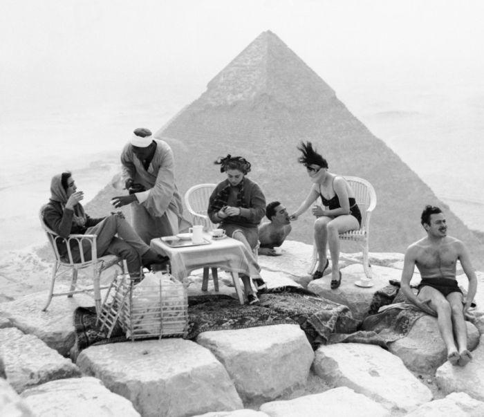 Группа туристов загорает на вершине Великих пирамид в Гизе.