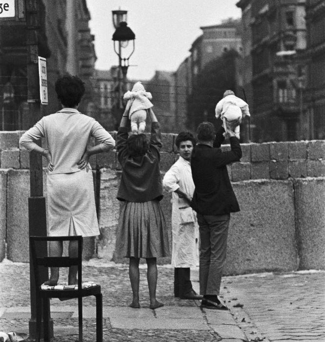 Пара показывает своих новорожденных детей дедушке с бабушкой по другую сторону Берлинской стены в 1961 году.