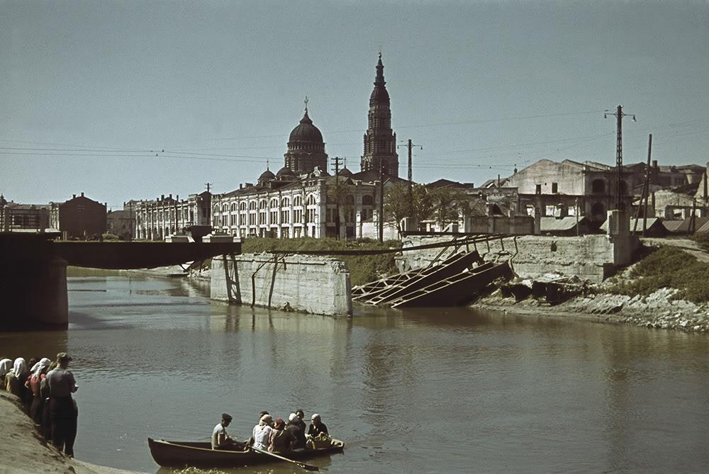 23. Лодочная переправа через реку Лопань. На фоне — взорванный при отступлении советских войск мост и Благовещенский собор.