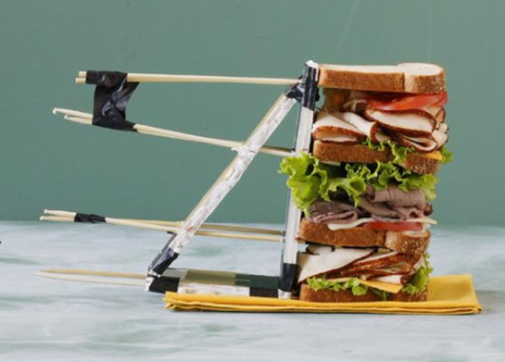 Им нужна опора. Позади этих аппетитных бутербродов скрывается произведение инженерного искусства, которое поддерживает структуру. Вся конструкция зафиксирована клейкой лентой, зубочистками и картоном.