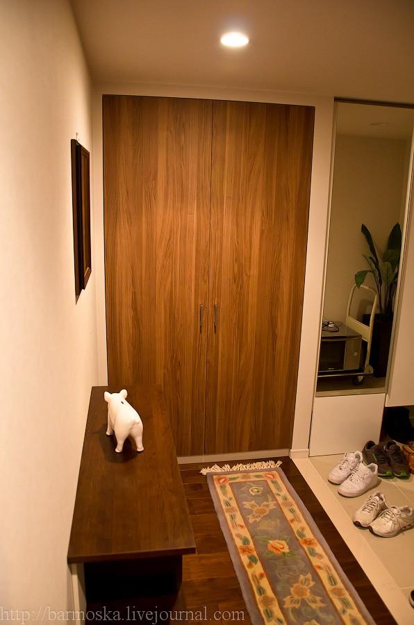 16. Вот наконец-то добрались до самой квартиры. Я попробую объяснить планировку, как получится. Справа виднеется белый порожек, где все оставляют обувь, — это вход. Я стою в коридоре, ведущем в остальную квартиру. В прихожей еще прямо по курсу имеется шкаф.
