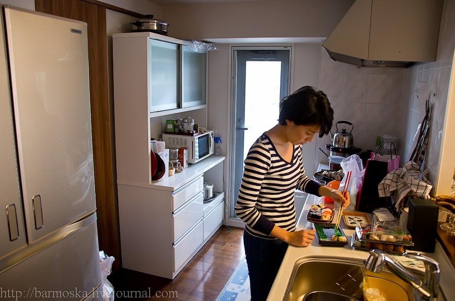 23. Проходим дальше. По левую руку — кухня, где хозяйка готовит нехитрый обед. На кухне есть выход на маленький балкончик. Большой холодильник side-by-side, вытяжка над плитой… не очень много шкафчиков для хранения утвари — собственно, поэтому на виду стоит здоровая кастрюля. За холодильником еще одна дверь — ведет в ванную. То есть фактически в ванной комнате две двери — одна из коридора (фото номер 20) и вторая из кухни.