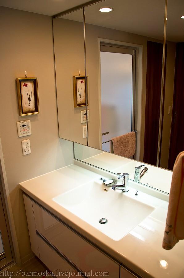 25. Теперь давайте заглянем в ванную комнату (снято из кухонной двери). Большая раковина, зеркальные шкафчики для хранения косметических продуктов. Слева на стене вспомогательный пульт управления для ванной — функциями сушилки, сауны или кондиционера можно управлять и отсюда. Дверь непосредственно в саму ванную отражается в зеркале.