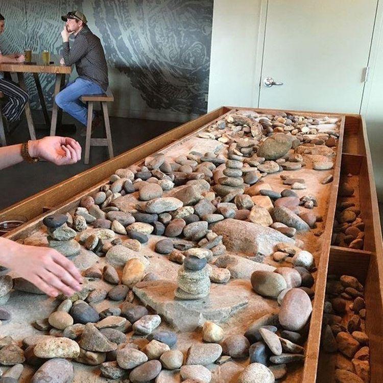 В этой пивоварне есть стол, специально предназначенный для строительства пирамид из камешков